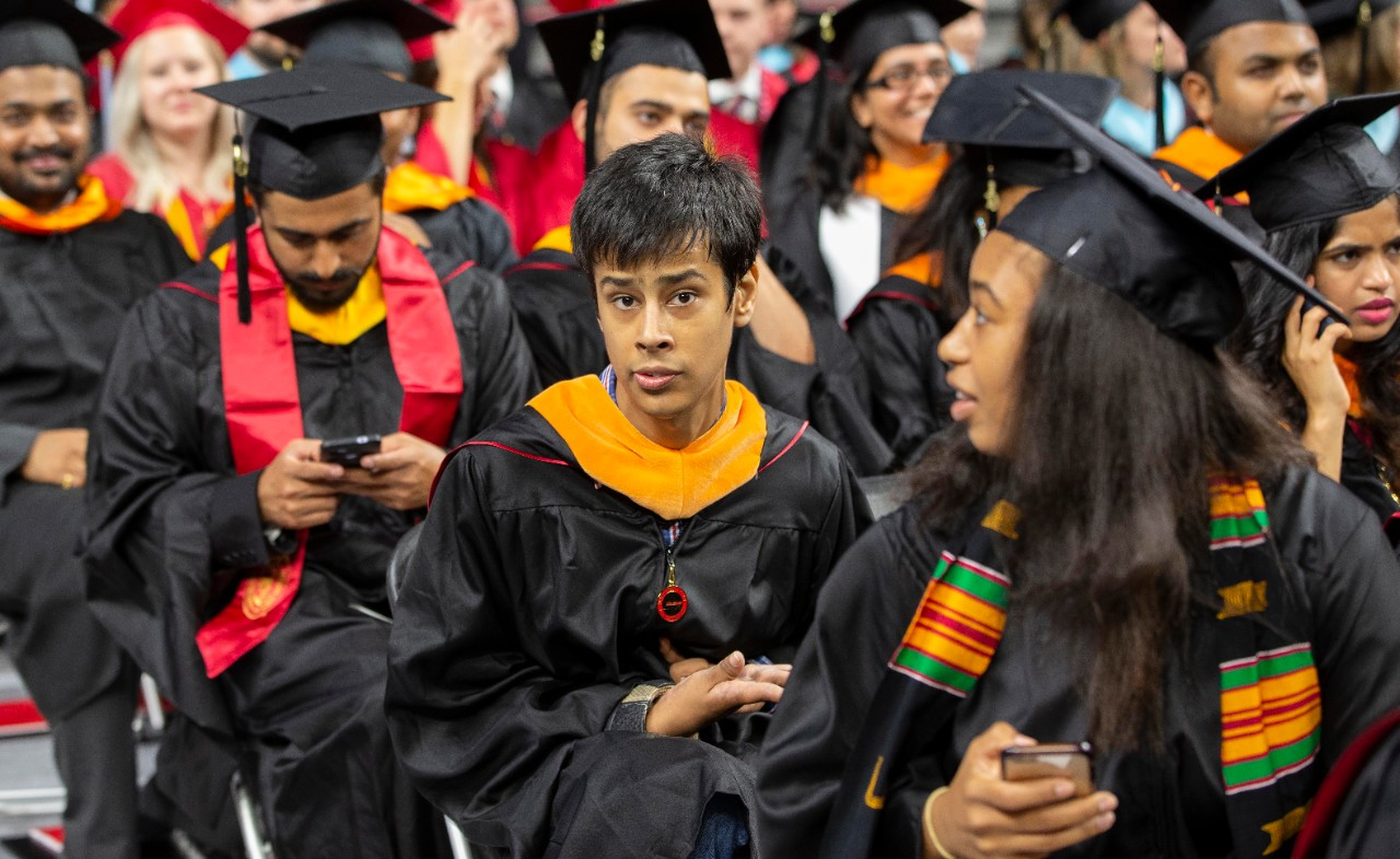 Sidhart Taneja sits in his graduation attire at Fifth Third Arena.