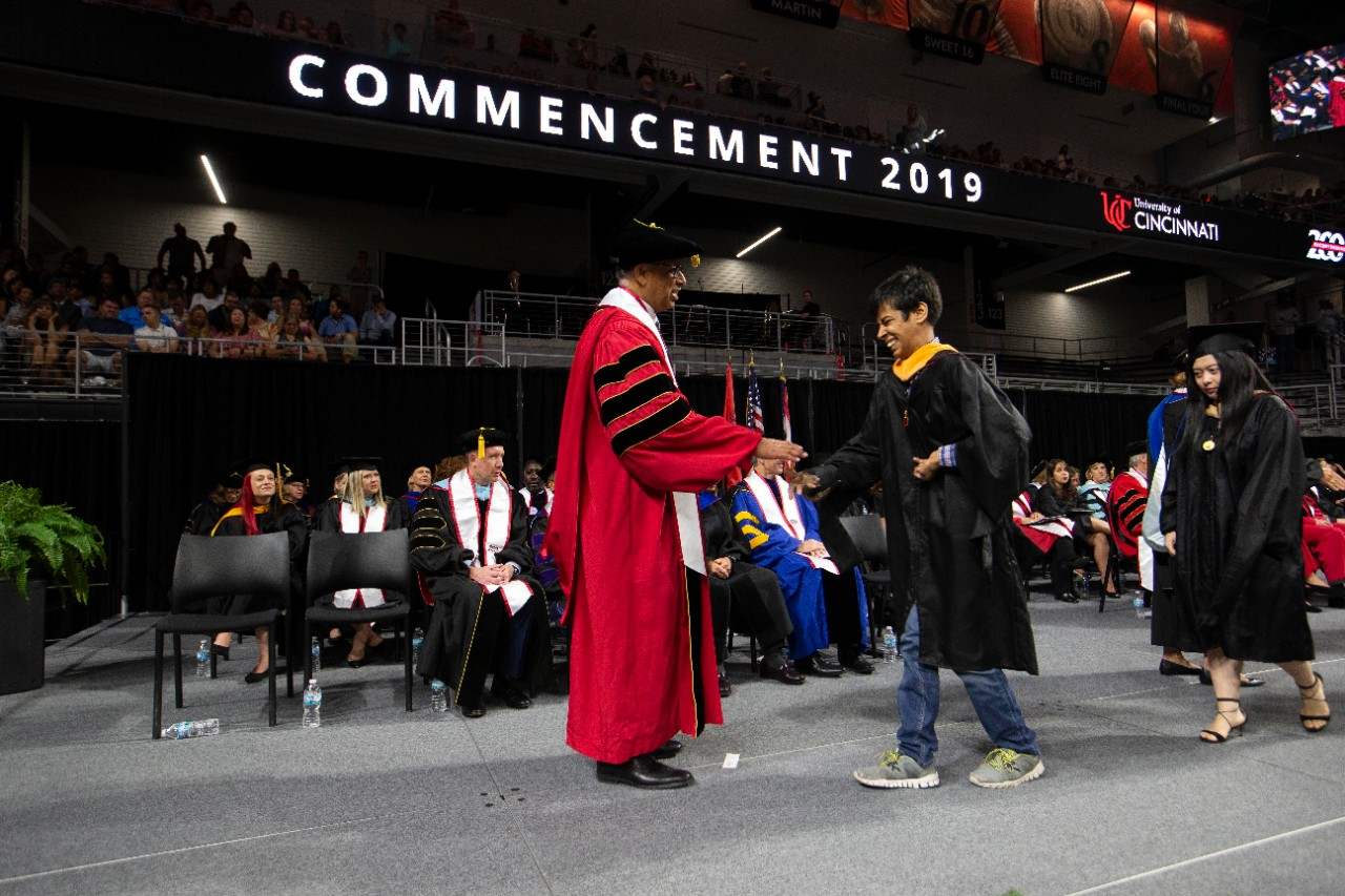 President Neville Pinto congratulates Sidharth Taneja on stage during commencement at Fifth Third Arena.
