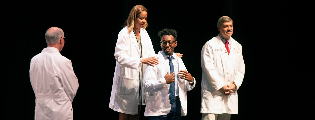 Mia Mallory, MD, places a white coat on incoming medical student Austin Thompson at the 2019 White Coat Ceremony.