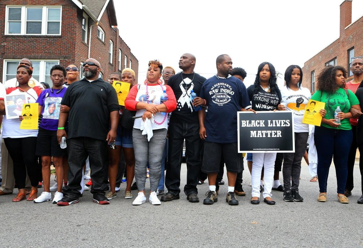 "protestors stand in a line holding signs saying ""black lives matter"""