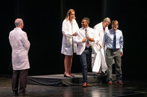 Adam Butler receives a white coat from Mia Mallory, MD, while Francis Calebrese interacts with Philip Diller, MD, PhD.