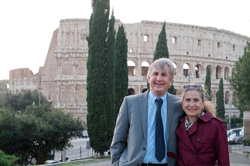 A man and woman standing in front of Roman ruins