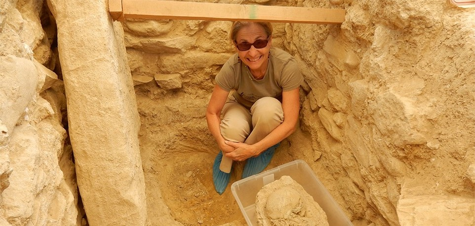 A woman sits in an archaeological grave