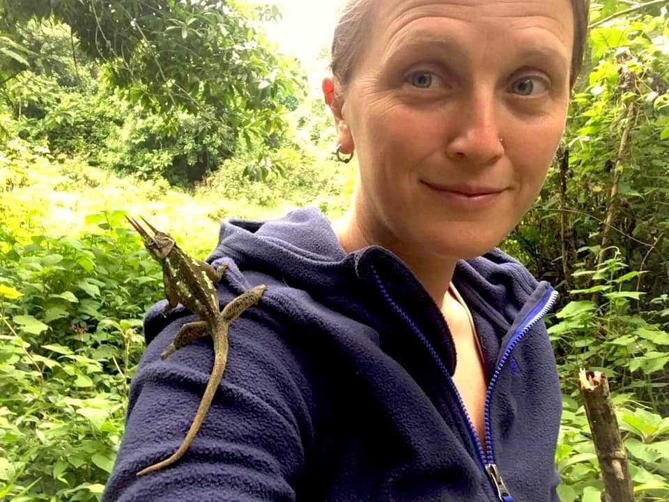 Lucinda Lawson takes a picture of herself with a chameleon on her shoulder.