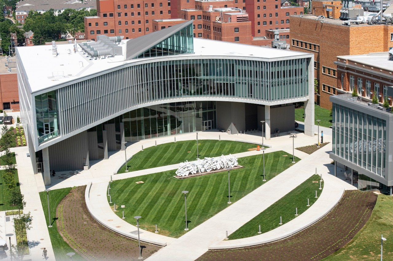 An exterior view of the Health Sciences Building, including a green space, sculpture and walkways in front of the building.