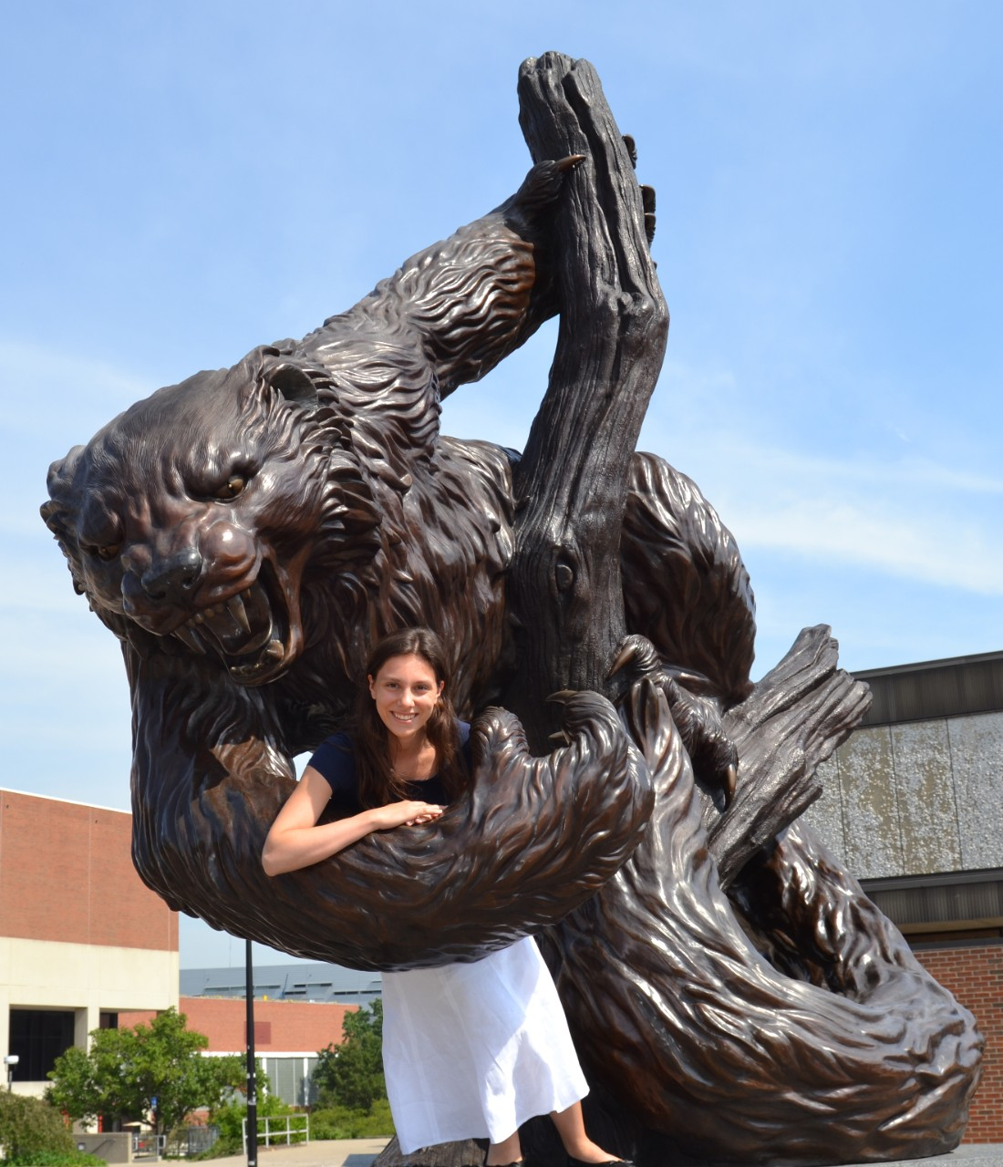 A young woman stands leaning on a statue of the UC Bearcat mascot