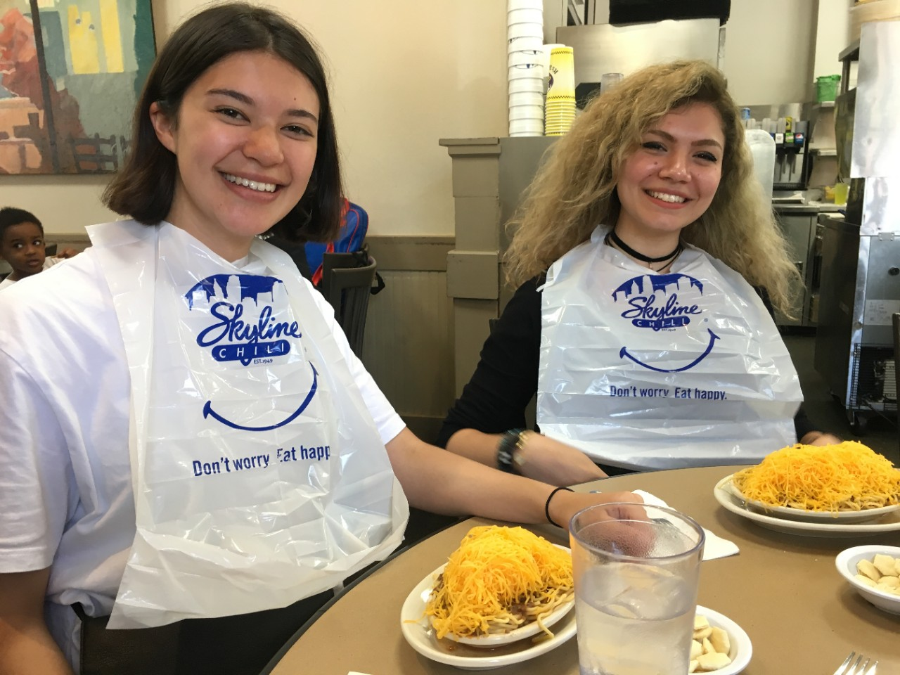 Two young women sit at a table eating Cincinnati chili