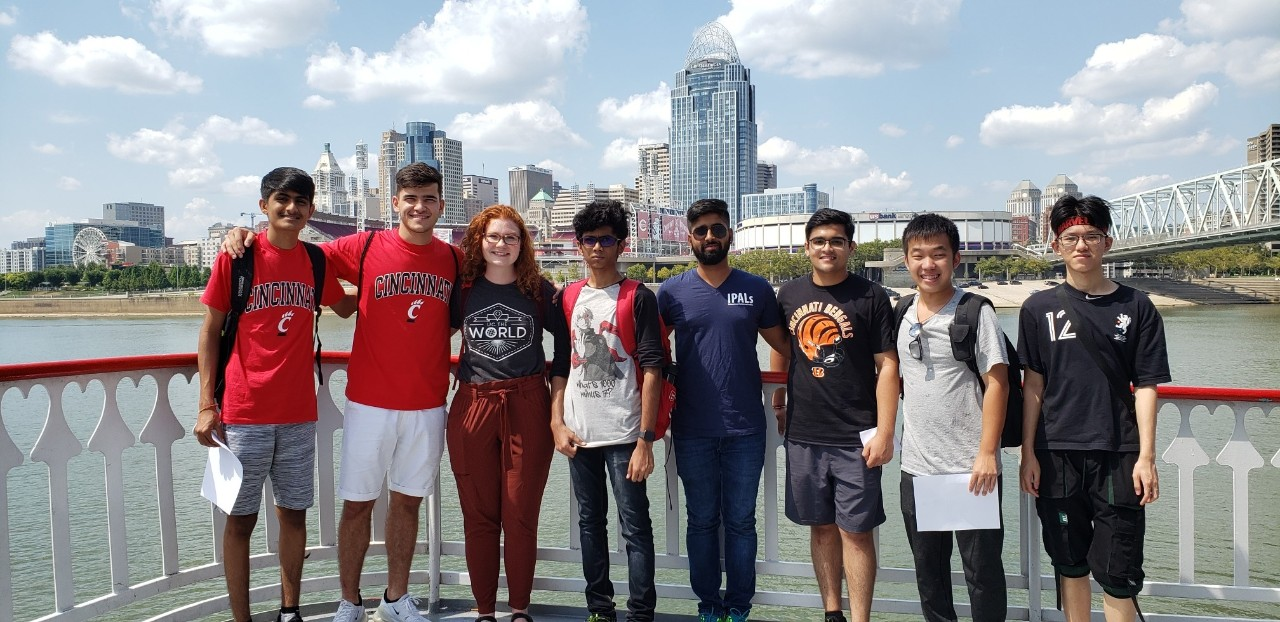 Students pose on a riverboat with the Cincinnati cityscape in the background