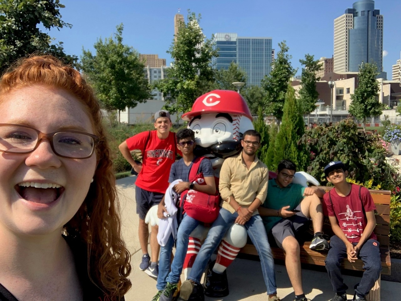 Students pose for a selfie with Mr Red statue