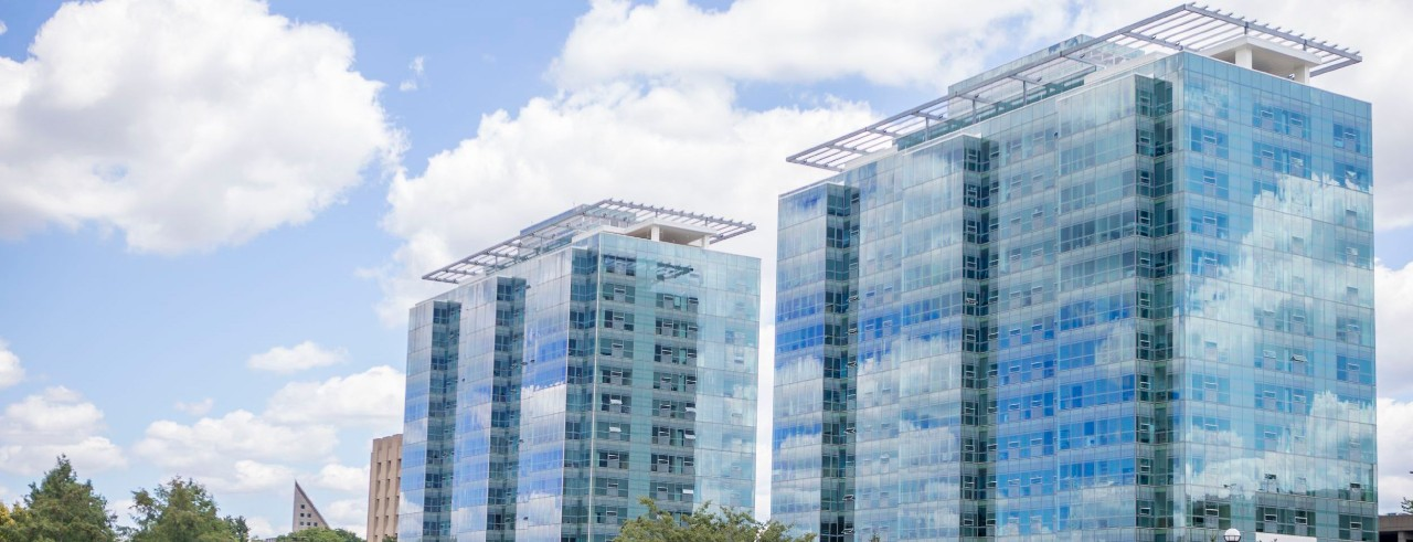 Two glass-enclosed buildings reflcting the sky
