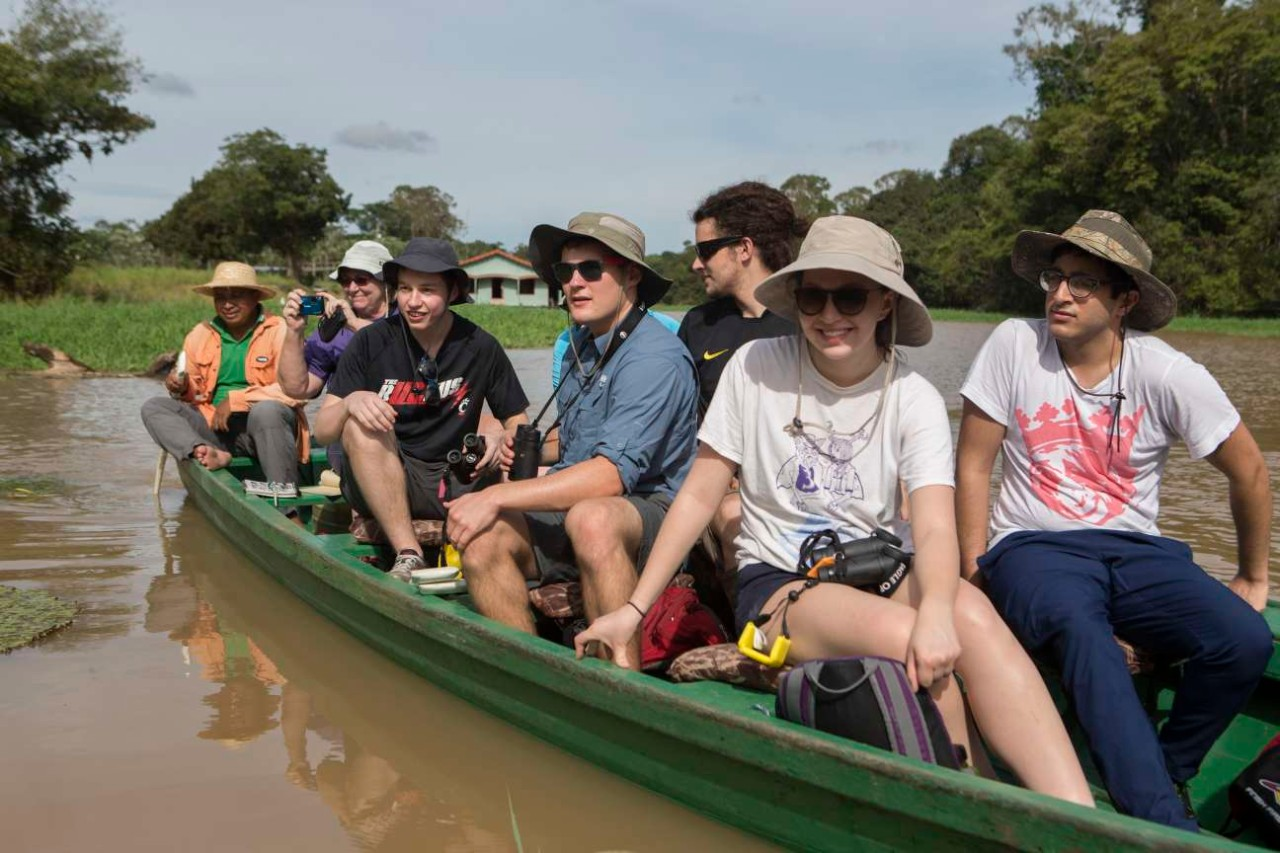 UC students canoe down a river in the Amazon.