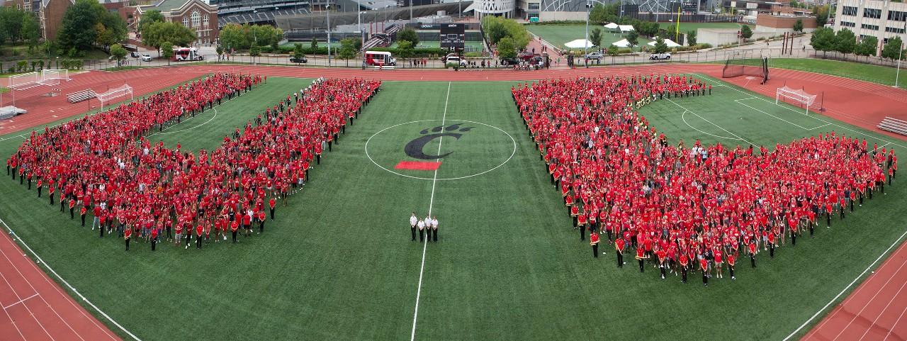 """Thousands of students in red form the letters """"UC"""" on a soccer field"""