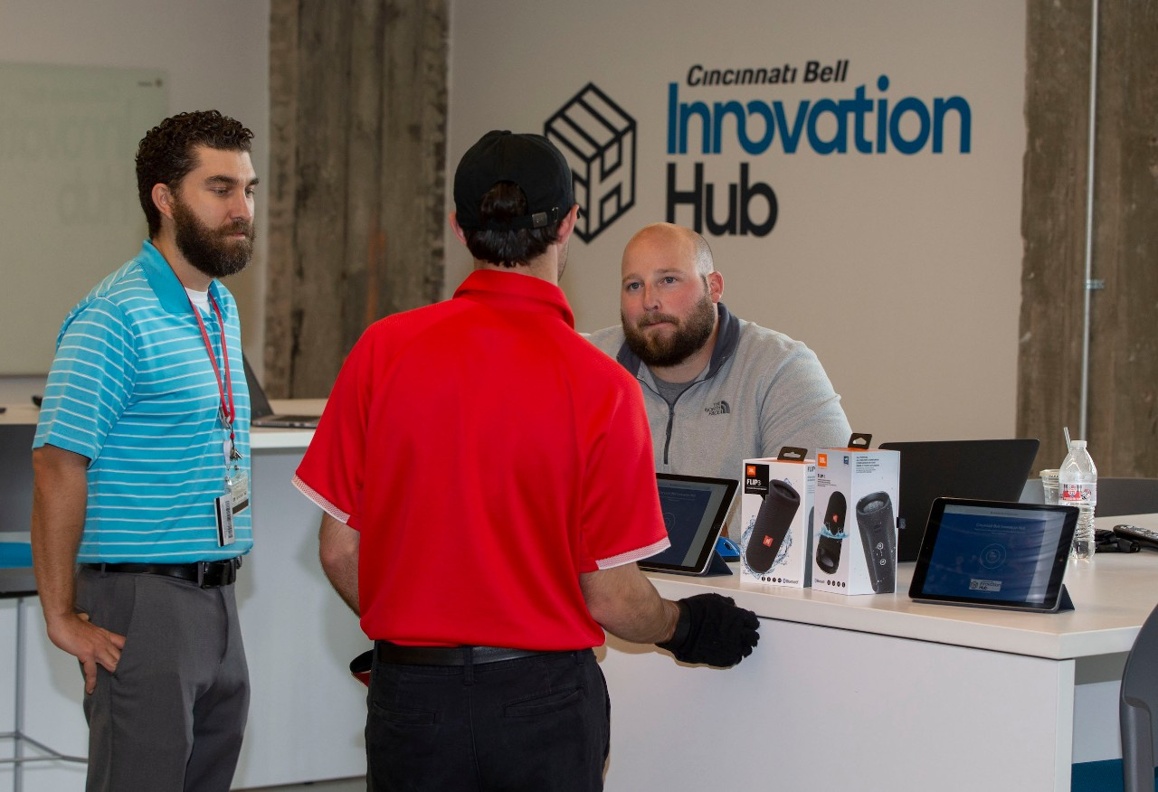 "Two men talk to a third man behind a desk. The logo for ""Cincinnati Bell Innovation Hub"" appears in the background."
