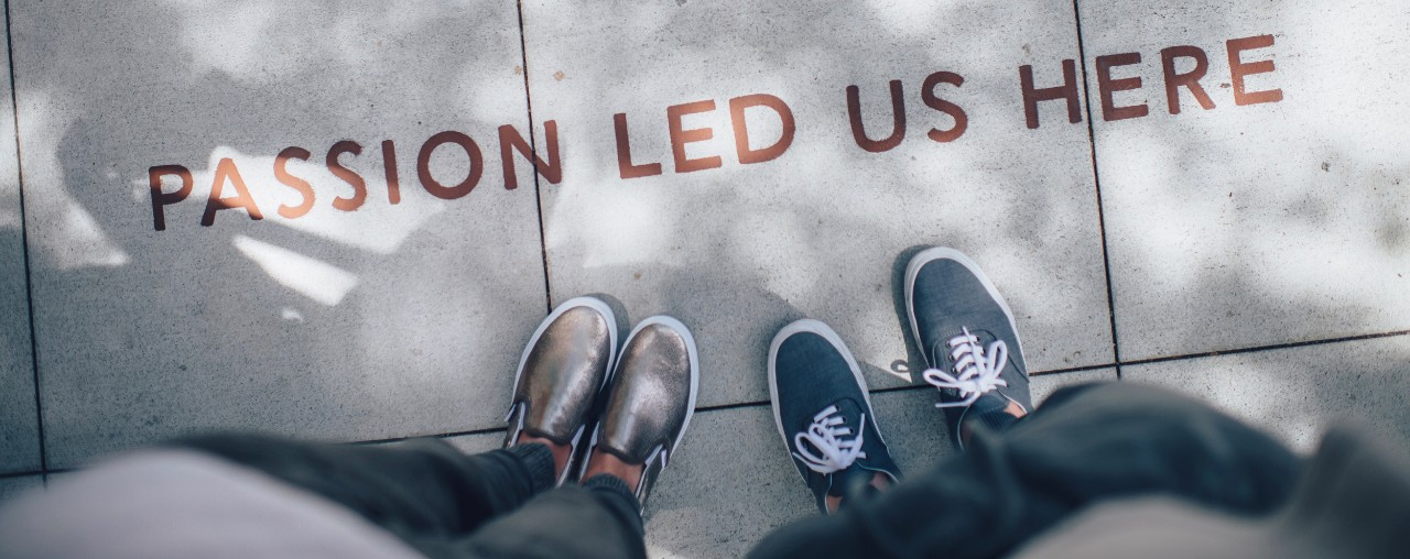 """Shoes on sidewalk pavement with the words, """"Passion Led Us Here,"""""""