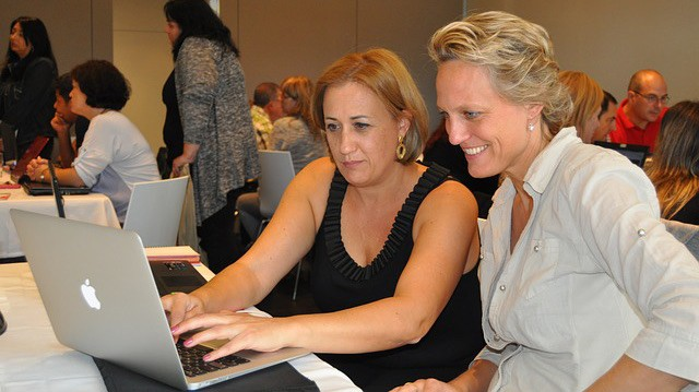 Two women work on a laptop in a classroom.