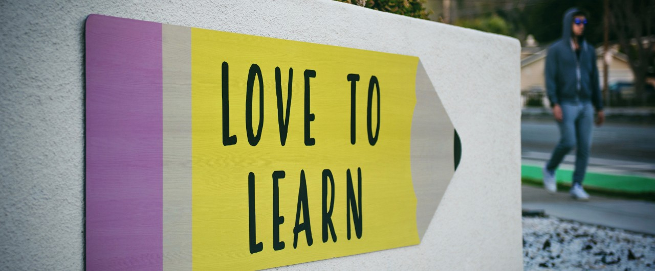 "Large fence sign painted like a pencil with the words, ""Love to Learn."""