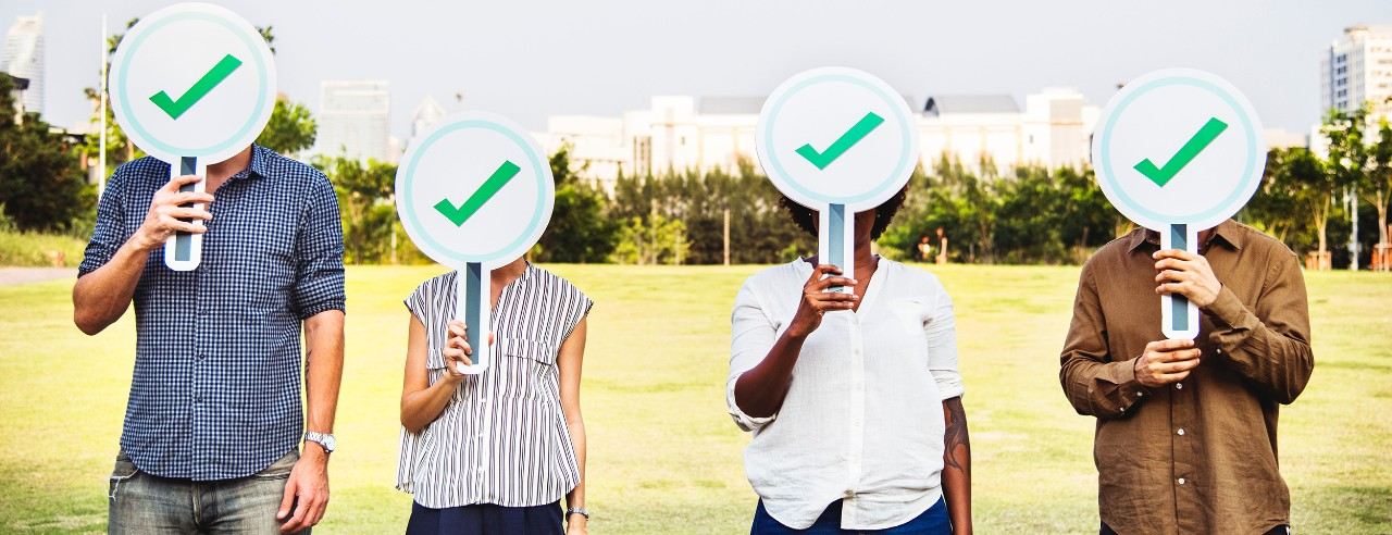 Four people holding checkmark signs over their faces