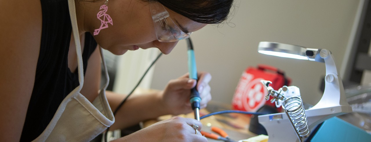 Close-up of a student using a soldering tool