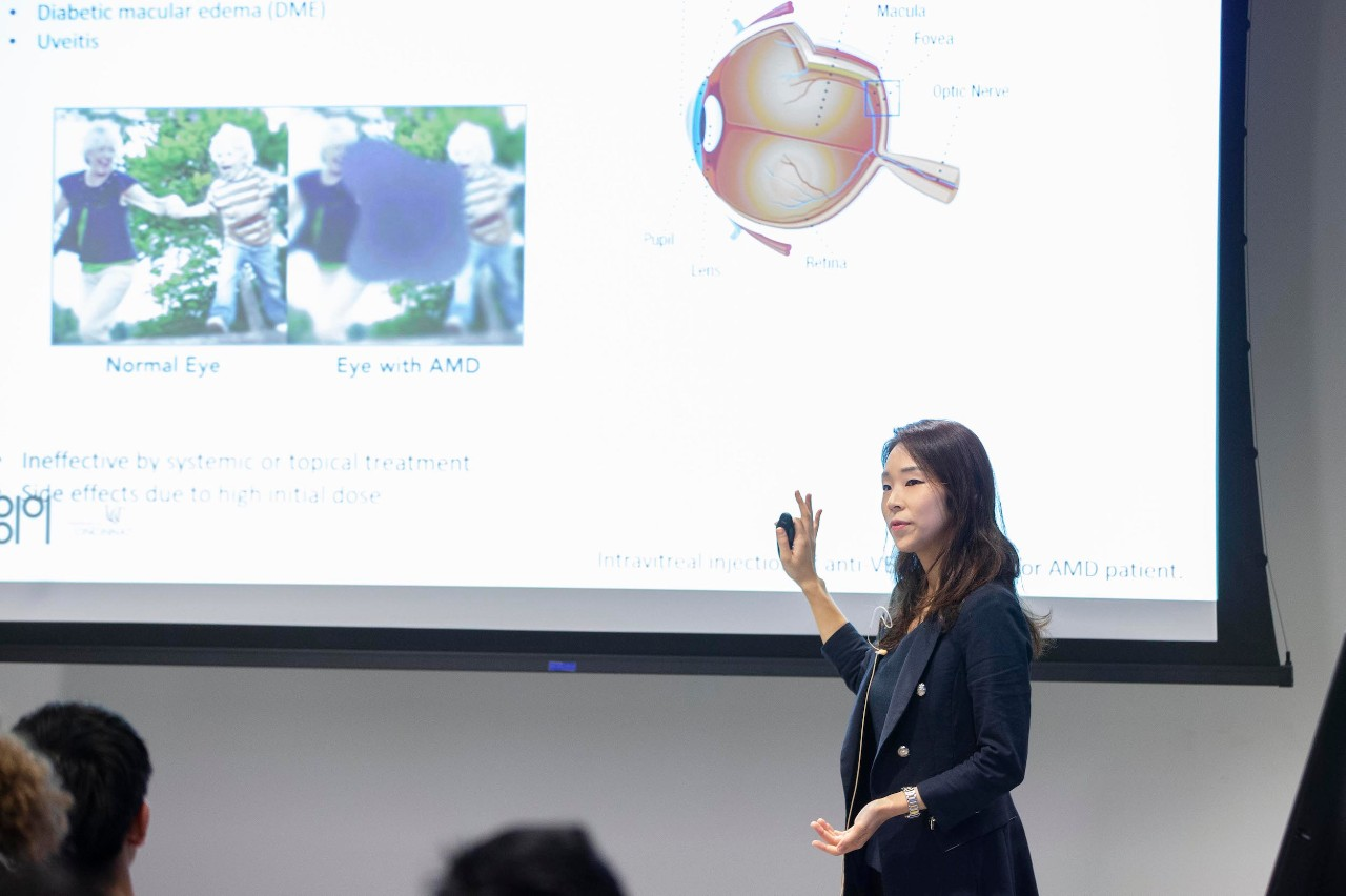A woman gives a presentation in front of a large video screen