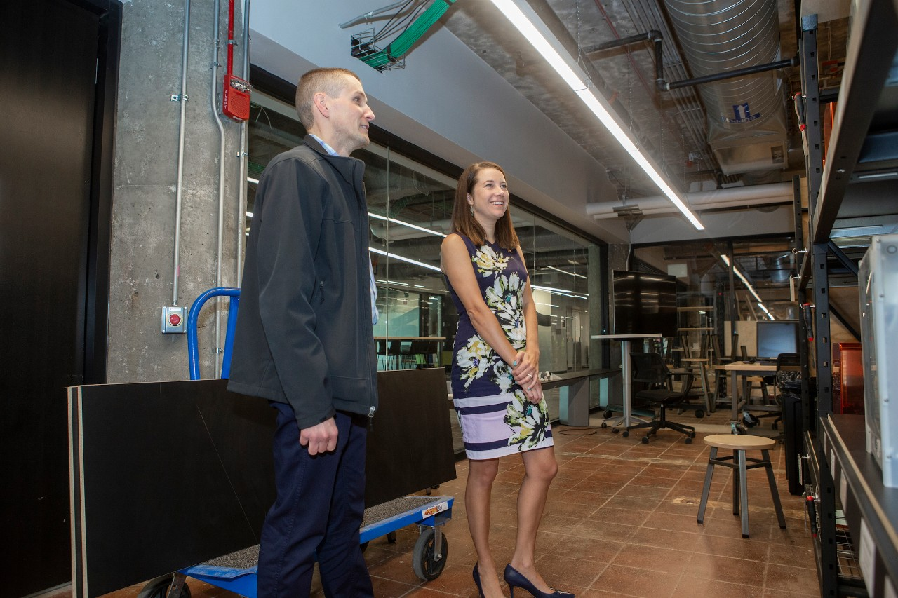 A man and a woman standing in a room looking at 3d printers