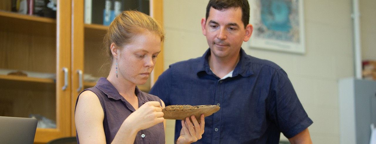 UC professor Joshua Miller and graduate student Abby Kelly examine a fossilized horse jaw in his paleontology lab.