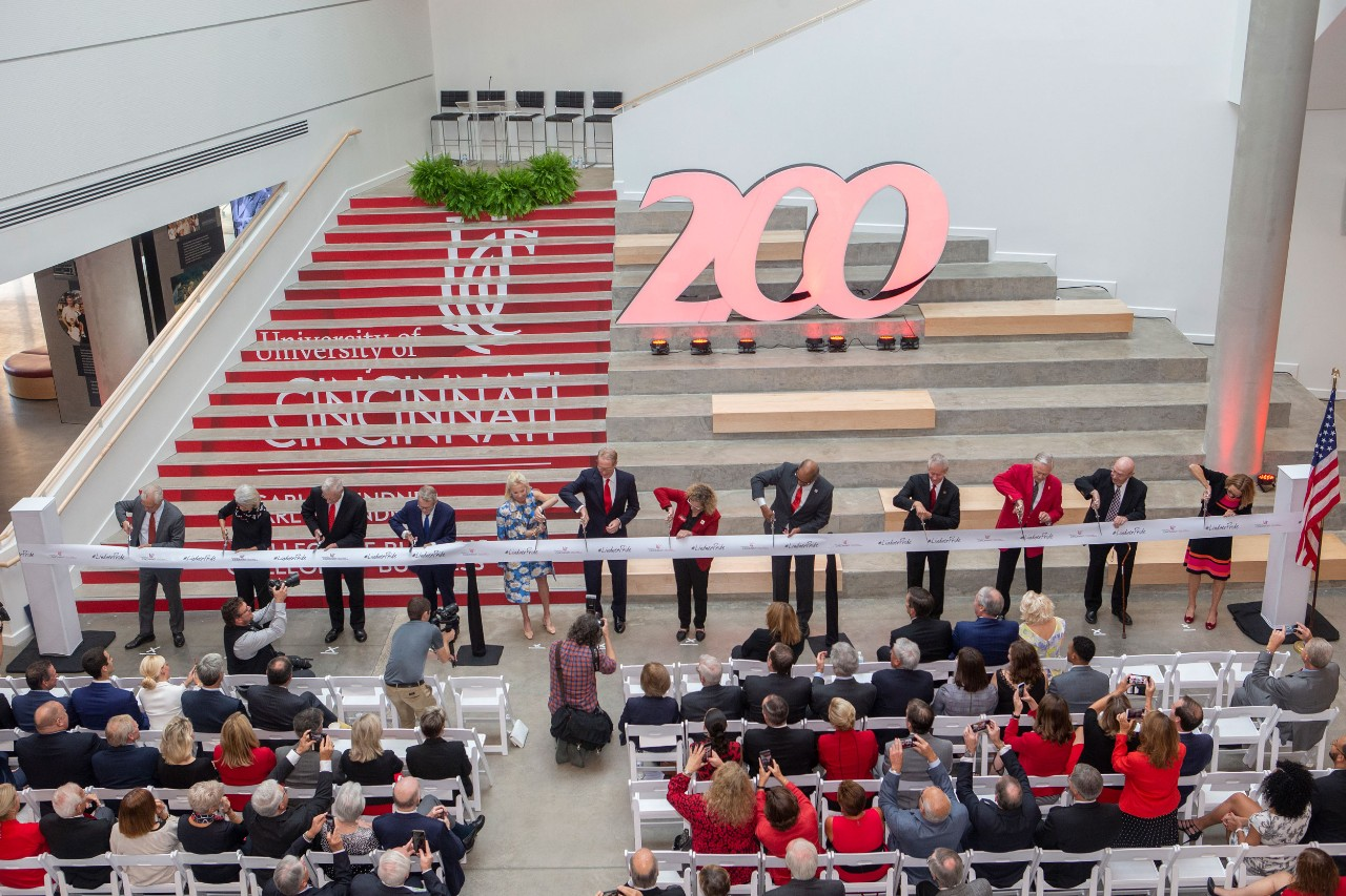 a row of people line up in a large atrium and cut a large ribbon with pairs of ceremonial scissors