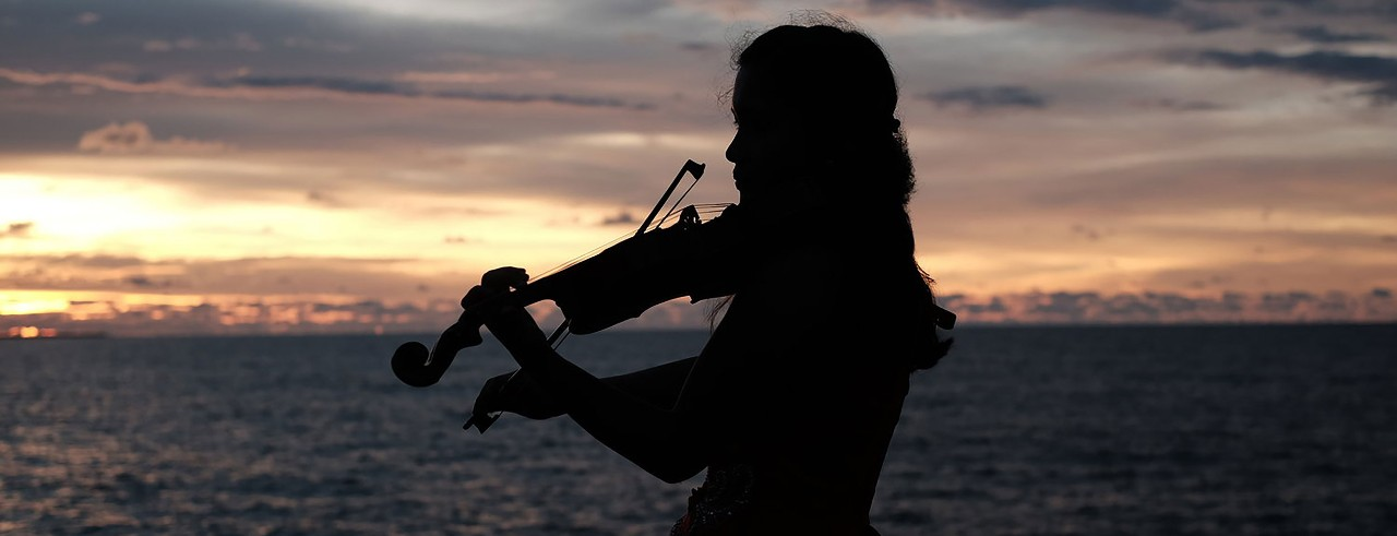 KayCee Galano practices her violin while at the beach