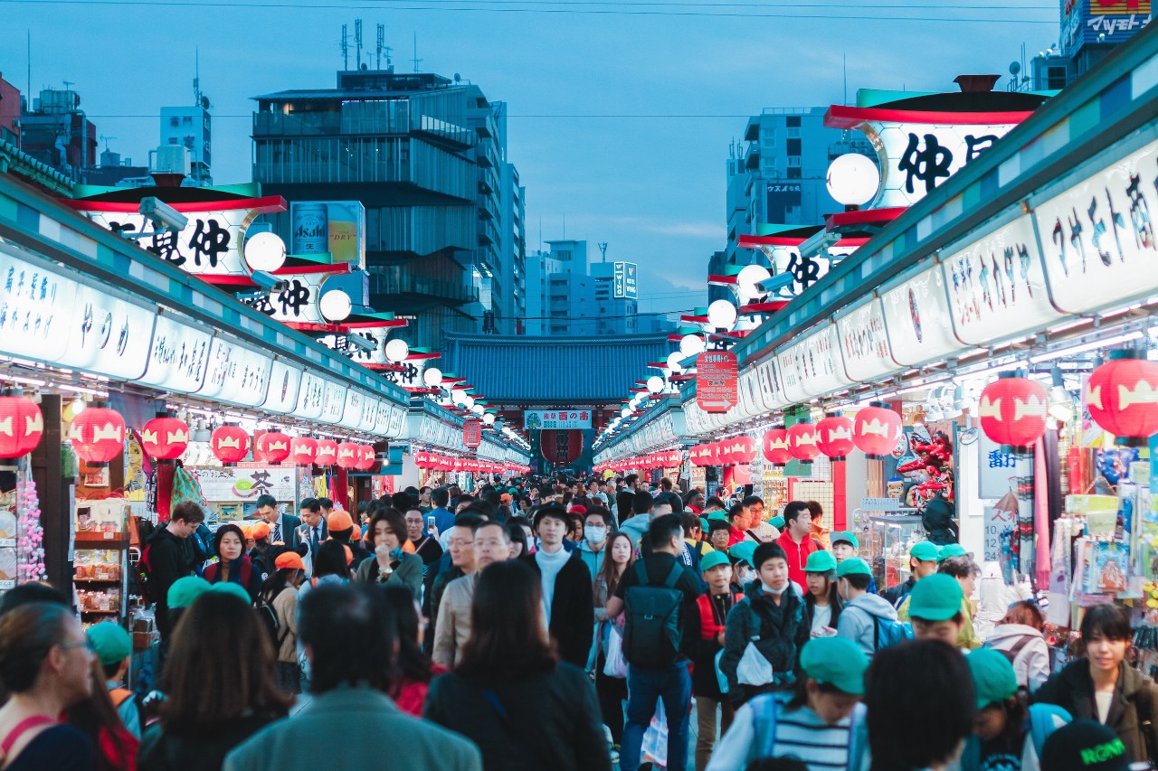 A crowded street market in Tokyo, Japan, at dusk.