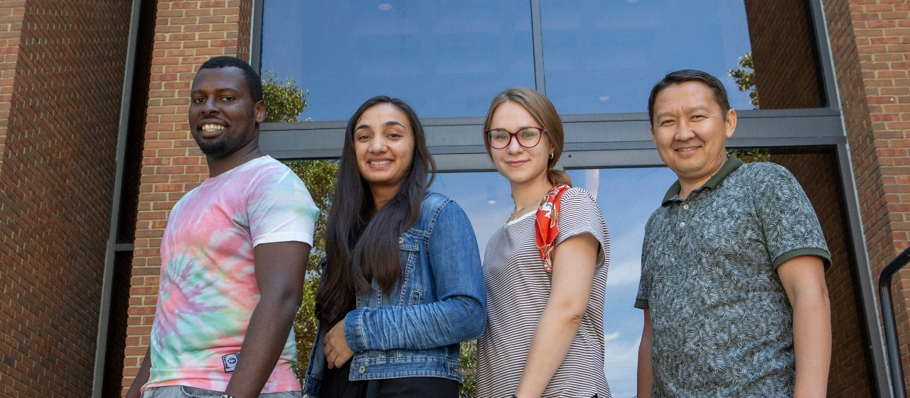 Four students pose in a line
