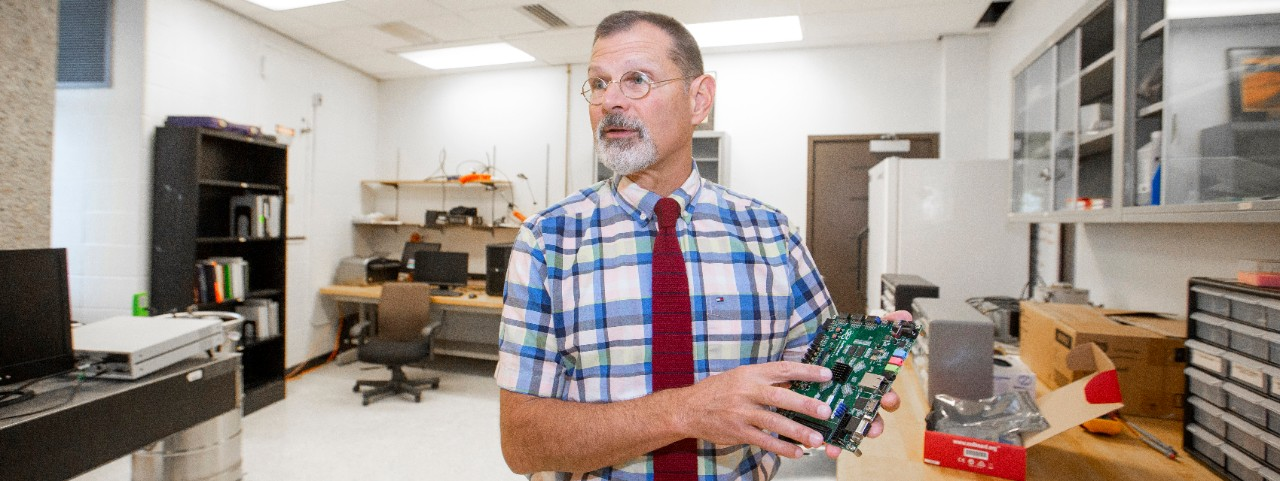 UC engineering professor John Emmert holds up a circuit board in a lab.