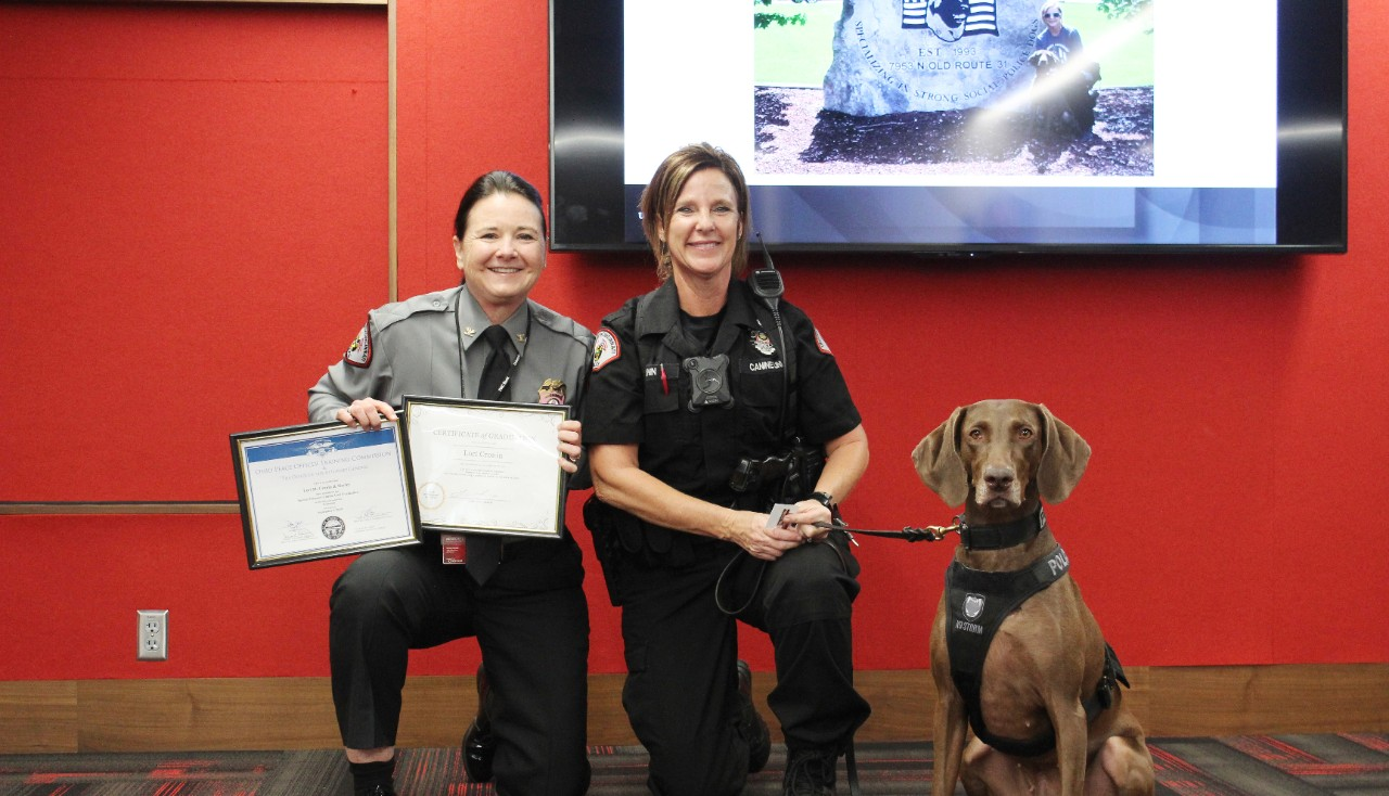 UCPD Chief Maris Herold poses with Officer Lori Cronin and K9 Harley.