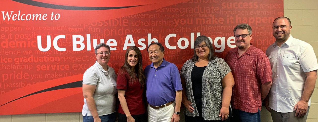 """Six men and women stand in front of a sign reading, """"Welcome to Blue Ash College."""""""