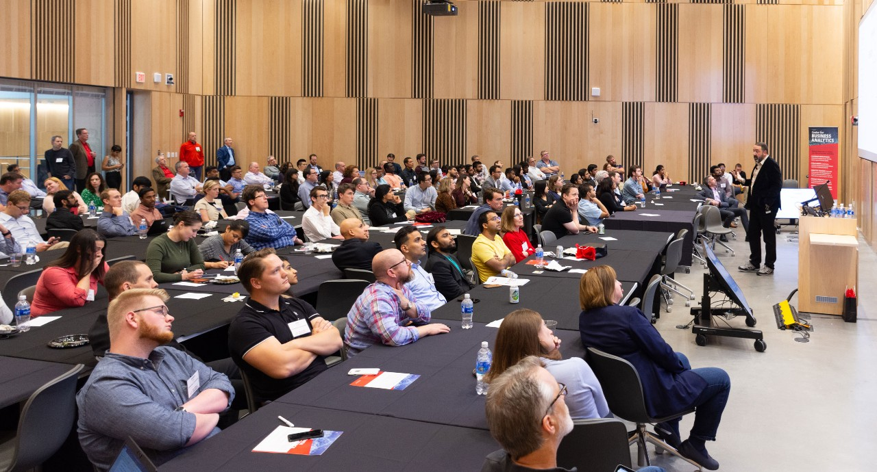 Symposium attendees sit in large conference room watching a man give a presentation