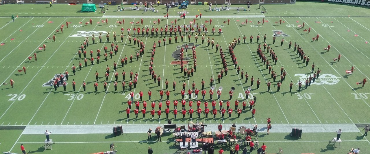 The UC Alumni Marching Band creates an outline of the number 200 with their bodies