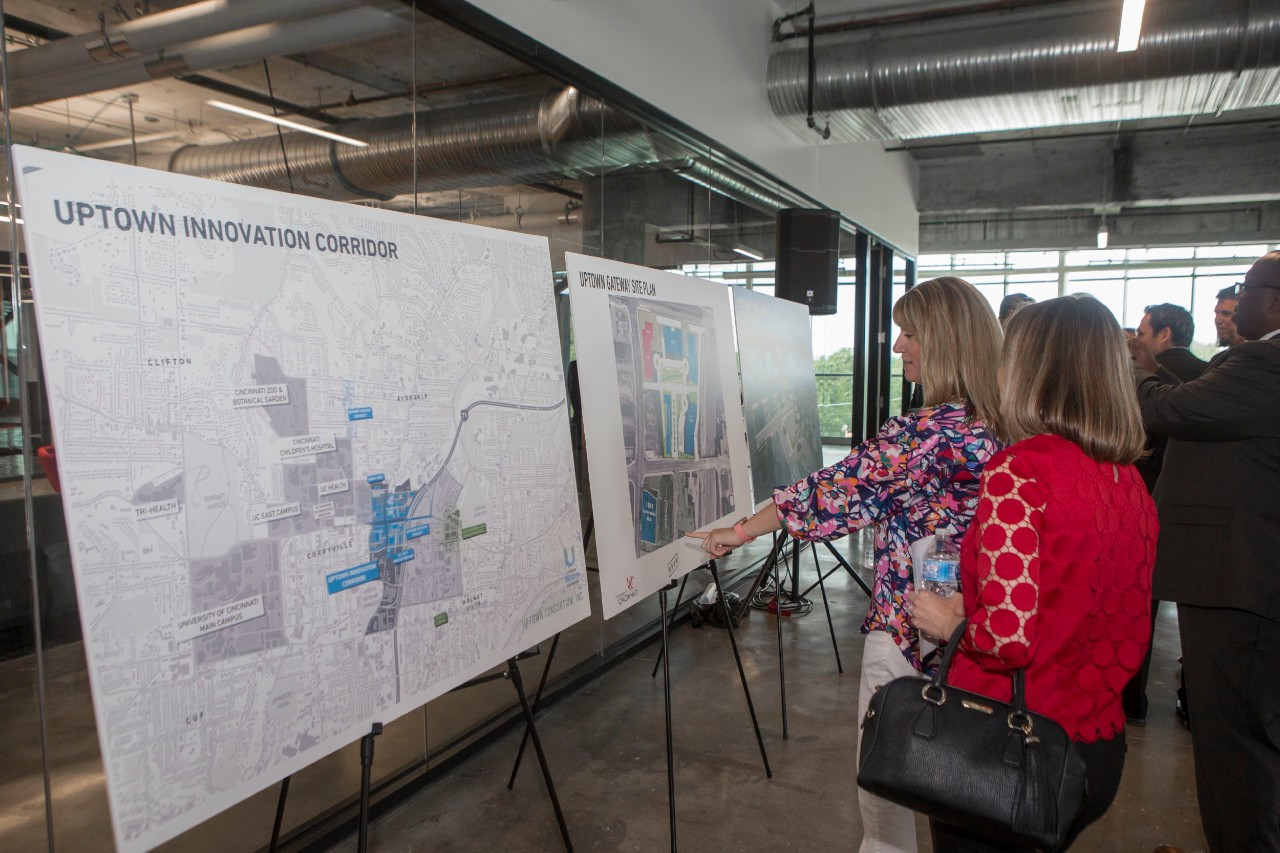 A crowd of people examine renderings and maps on large posterboards