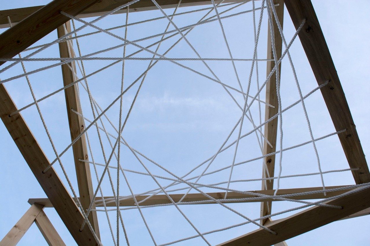 A view of the sky, looking through a sky light shaped in spirals of crossing metal beams