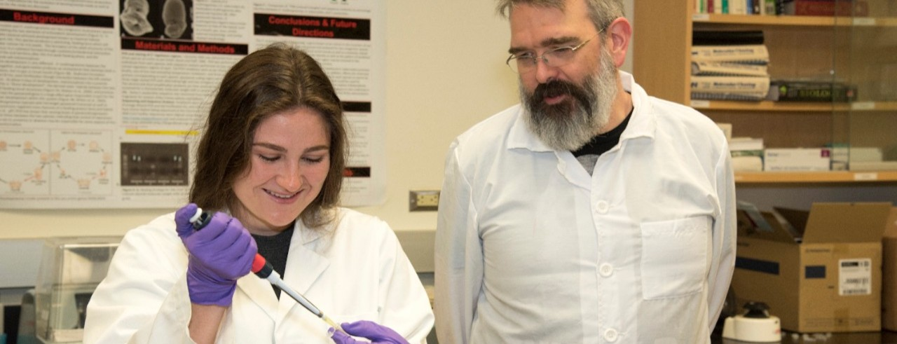 Student and professor in white coats work in a lab