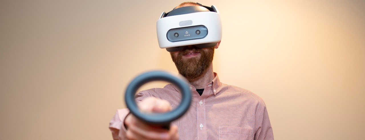 A man wearing a virtual reality headset and holding two virtual reality controllers