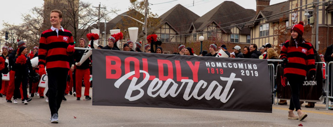 """Students lead a parade holding a banner that says """"Boldly Bearcat"""""""