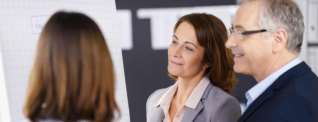 Business woman and business man looking at a flip chart with one other business woman.