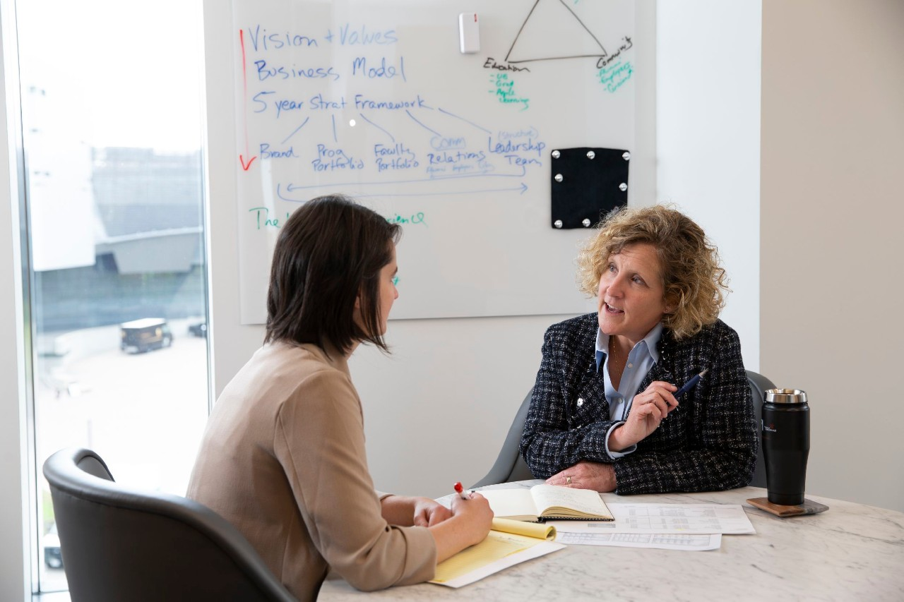 two women sitting at a table in an office