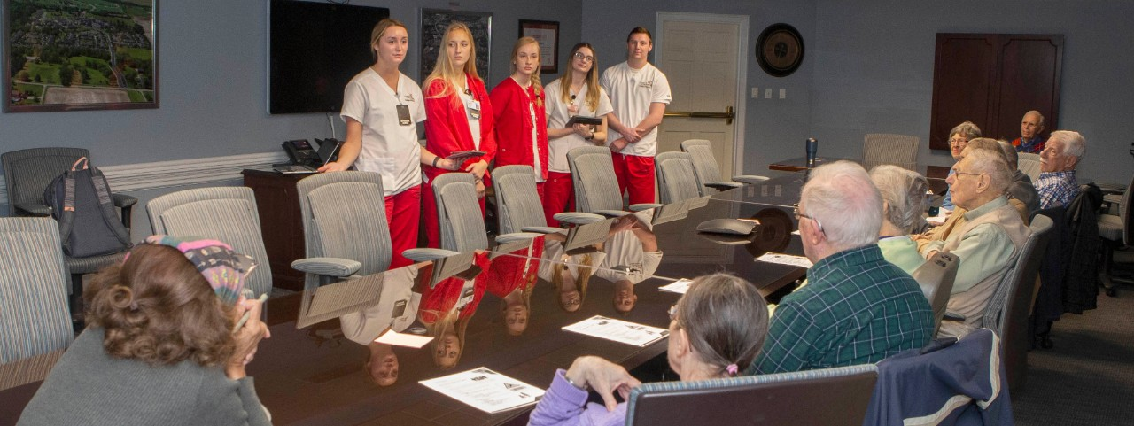 Five nursing students standing at a table across from several residents of Maple Knoll Village