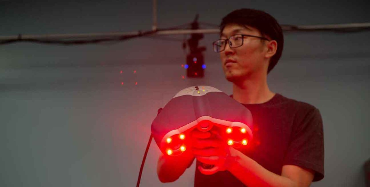 A UC student holds up a laser scanner that can help measure and render objects in three dimensions.