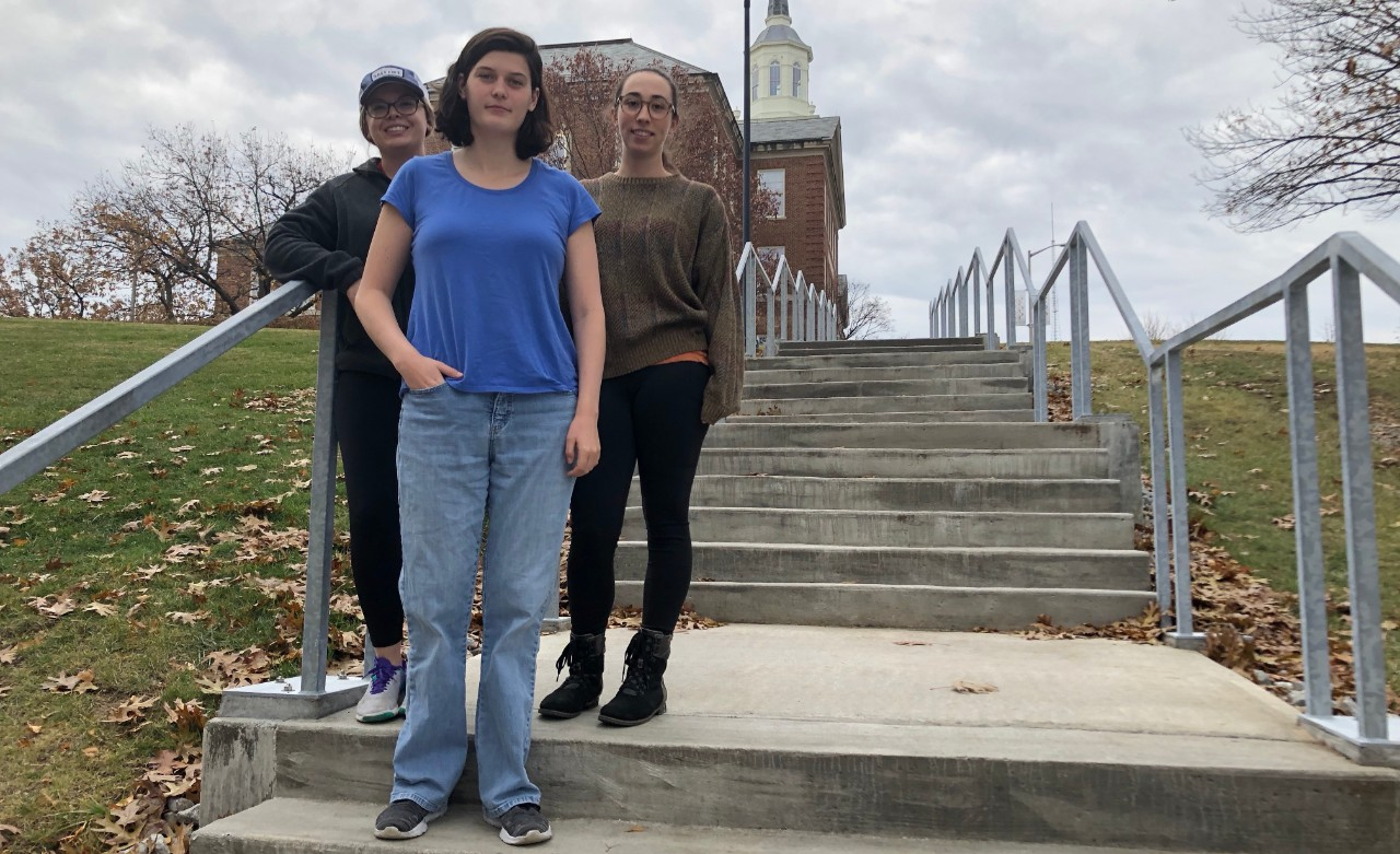 Students in Bob Hyland and Susanna Tong's bird diversity group (Mickaela Mohr, Emily Noeske and Zoe Gordon) pose in front of the steps connecting McMicken to Clifton Court.