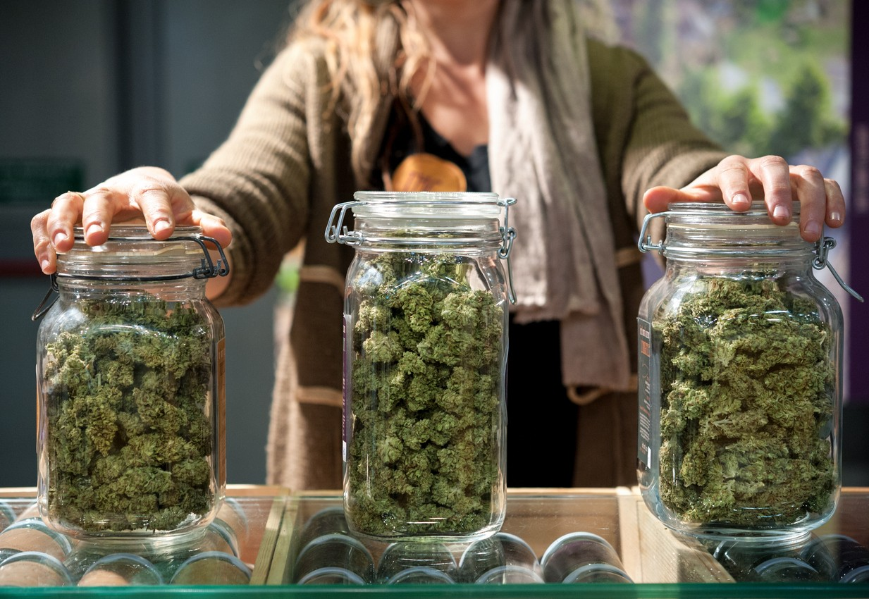 Glass jar full of Cannabis Sativa for sale at a market stall.