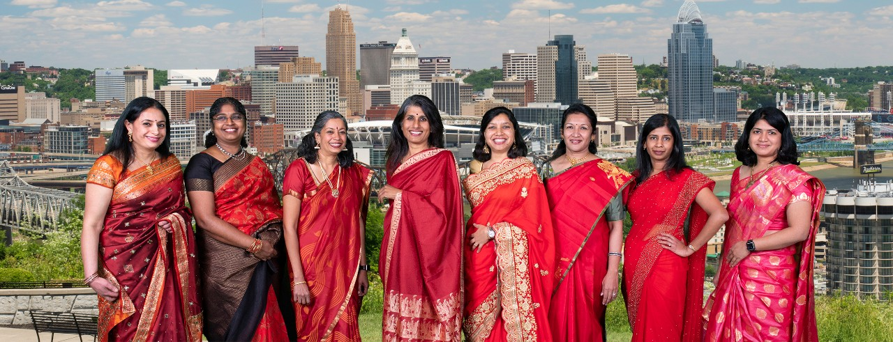 Image of eight women dressed in Red Sarees.