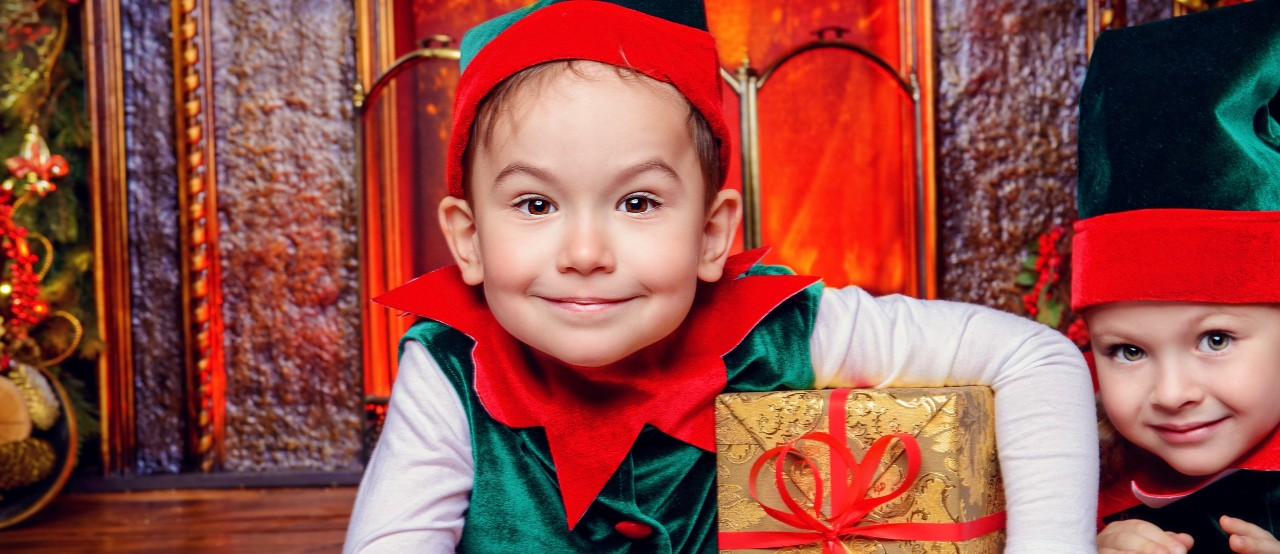 Two children dressed as Christmas elves smile while holding a wrapped present