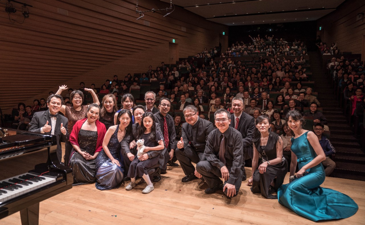 Alumni performers pose on stage in front of a full house at the Eslite Performance Hall in Taipei City, Taiwan.