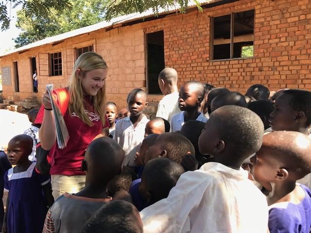 UC student talks with children in Tanzania.