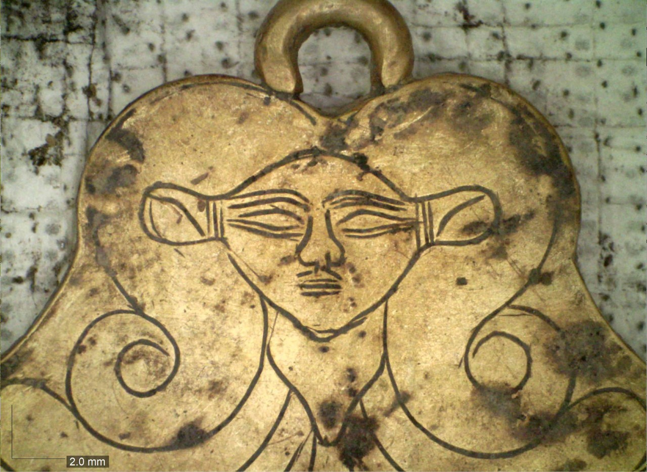 A gold pendant featuring the likeness of the Egyptian goddess Hathor.